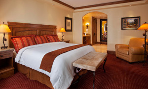 Siebert Suite king bed, Chair and walking bathroom featuring rich creams and red décor at our Vail hotel