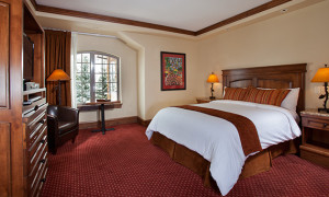 Vail Village room with window, king bed chair and tv armoire at Tivoli Lodge